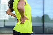 Woman wearing sportswear holding her painful lower back