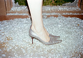 A woman wearing stilettos standing in broken glass