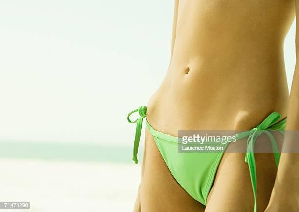 Woman wearing string bikini, close-up of abdomen