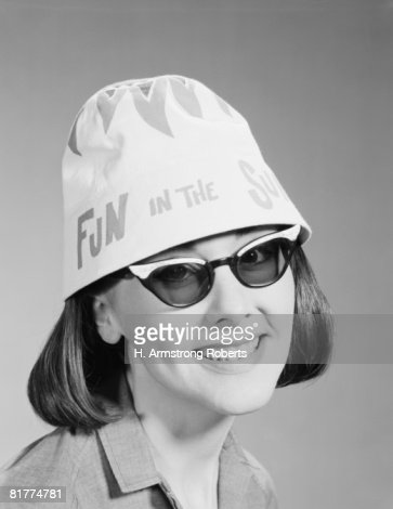 Woman wearing sunglasses and 'fun in the sun' hat, portrait.