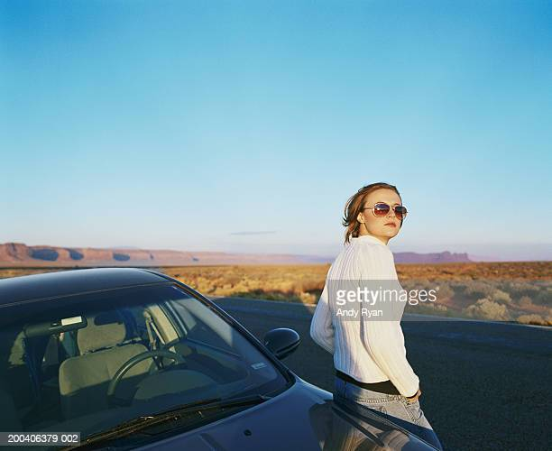 Woman wearing sunglasses leaning on car on desert road