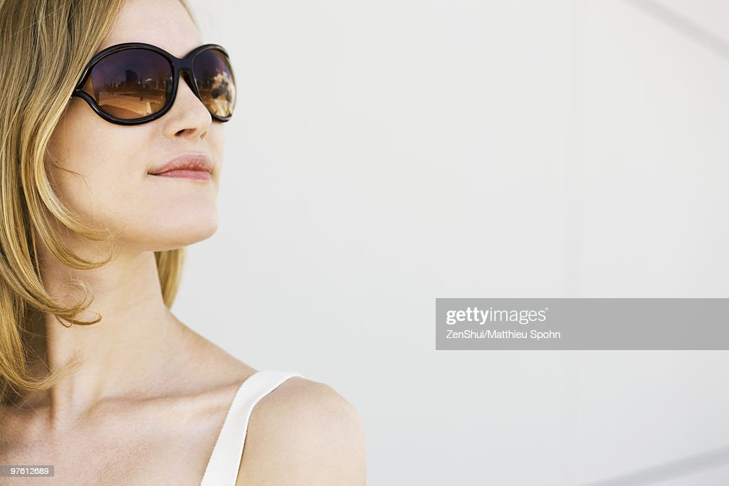Woman wearing sunglasses, looking away, portrait : Stock Photo