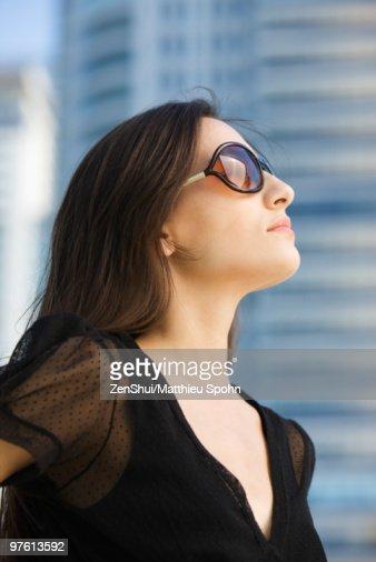 Woman wearing sunglasses, looking up, portrait