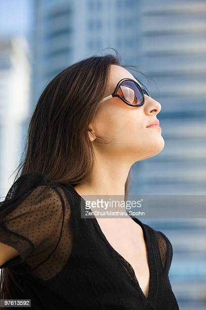 Woman wearing sunglasses, looking up, portrait