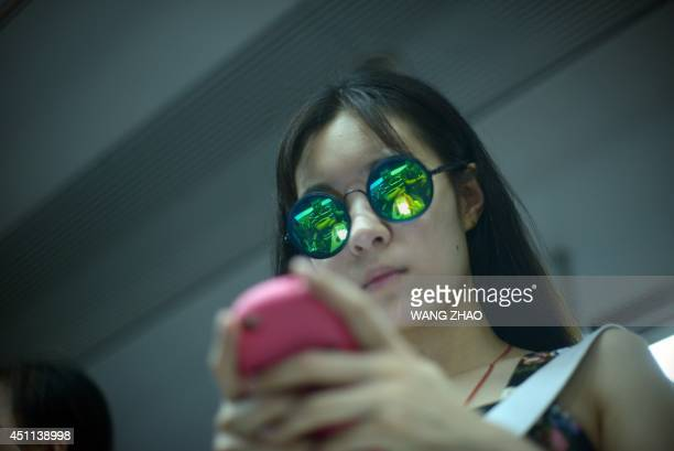 A woman wearing sunglasses plays with her mobile phone on a subway train in Beijing on June 24 2014 AFP PHOTO / WANG ZHAO