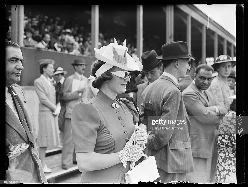 Woman wearing sunglasses, Royal Richmond Horse Show, June 1939. Woman in sunglasses, hat and gloves, standing with other spectators at the Royal Richmond Horse Show. Photograph by Edward G Malindine, taken from the photographic archive of the Daily Herald newspaper which comprises over 3 million photographs and covers a period from 1911 to the mid-1960s. The collection includes work by many famous photographers, who contributed assignments to the newspaper. The archive offers a fascinating photographic record of local, national and international events spanning these years, and is particularly rich in 1920s and 1930s photojournalism. It includes digitised images taken from glass plate negatives and from contact prints.