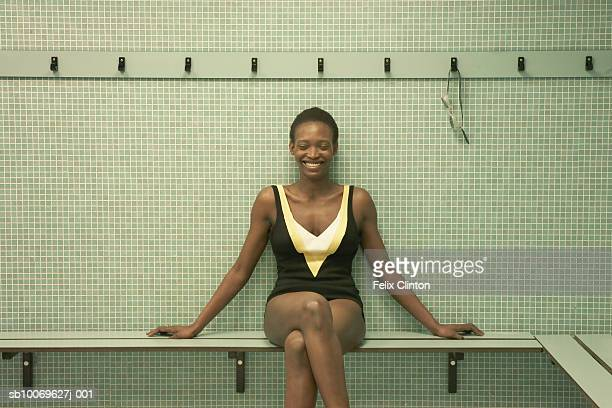Woman wearing swimsuit sitting in change room