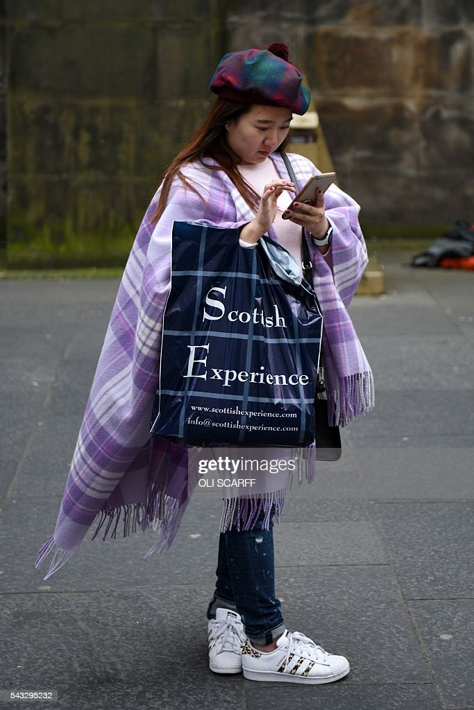 A woman wearing tartan checks her mobile phone in the city centre of Edinburgh, Scotland on June 27, 2016. Britain's historic decision to leave the 28-nation bloc has sent shockwaves through the political and economic fabric of the nation. It has also fuelled fears of a break-up of the United Kingdom with Scotland eyeing a new independence poll, and created turmoil in the opposition Labour party where leader Jeremy Corbyn is battling an all-out revolt. SCARFF