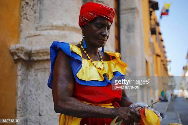 A woman wearing the Colombian colors sells fruit on the street in Cartagena Colombia on January 25 2017 / AFP / David GANNON