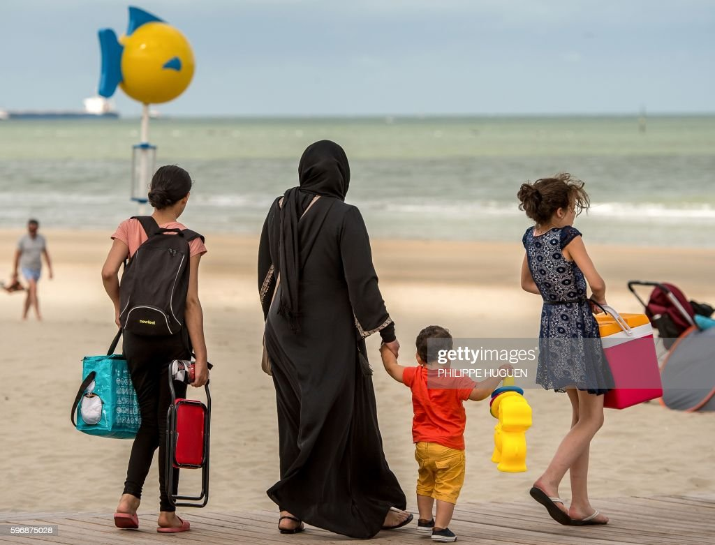 A woman wearing the islamic hijab walks with children on the beach in MaloLesbains northern France on August 28 2016 / AFP / PHILIPPE HUGUEN