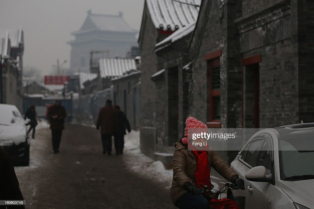 A woman wearing the mask rides through an alley near the Bell Tower during severe pollution on February 3, 2013 in Beijing, China. Houhai Lake is a popular place for winter sport and entertainment in Beijing.