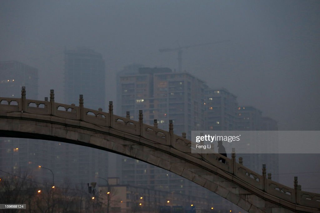 A woman wearing the mask walks on a bridge during severe pollution on January 18, 2013 in Beijing, China.