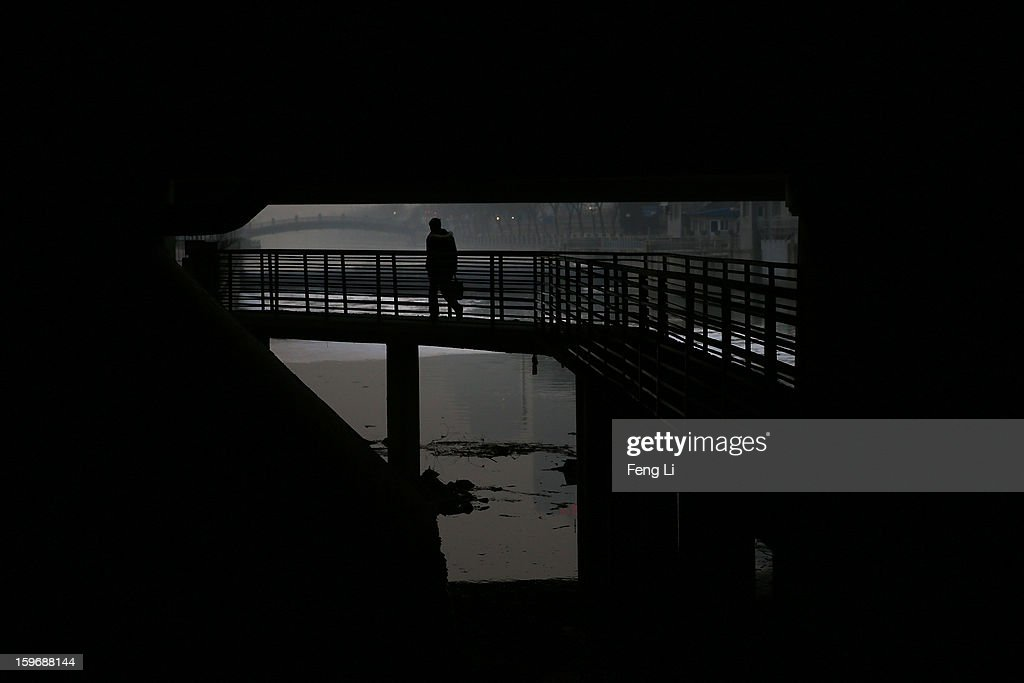 A woman wearing the mask walks under a bridge during severe pollution on January 18, 2013 in Beijing, China.