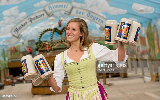 A woman wearing the traditional Bavarian Dirndl presents the offical Oktoberfest beer mugs at the Oktoberfest grounds in Munich southern Germany on...