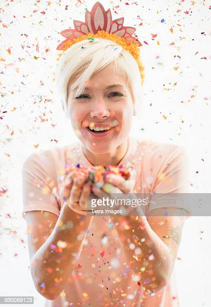 Woman wearing tiara blowing confetti