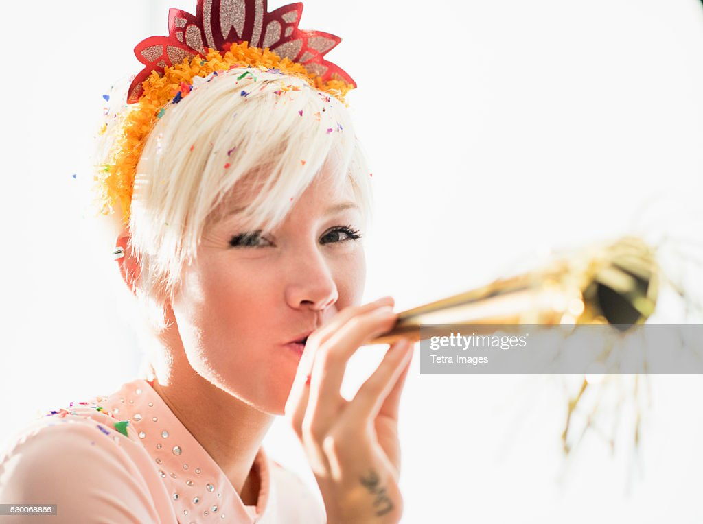 Woman wearing tiara blowing party horn blower