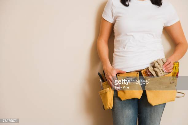 Woman wearing tool belt and leaning against wall indoors