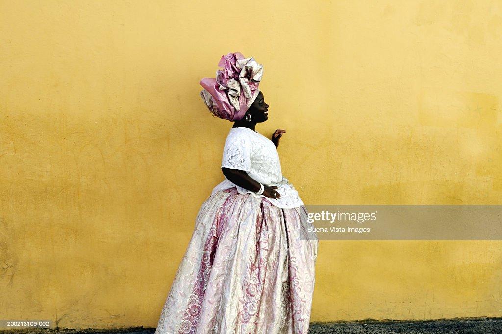Woman wearing traditional Brazilian clothing, standing by yellow wall