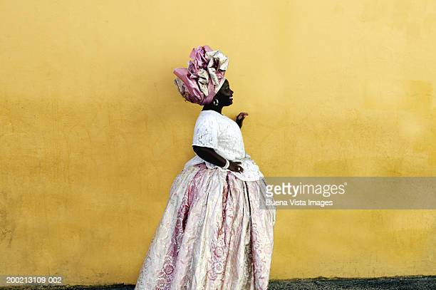 Woman wearing traditional Brazilian clothing, standing by yellow wall