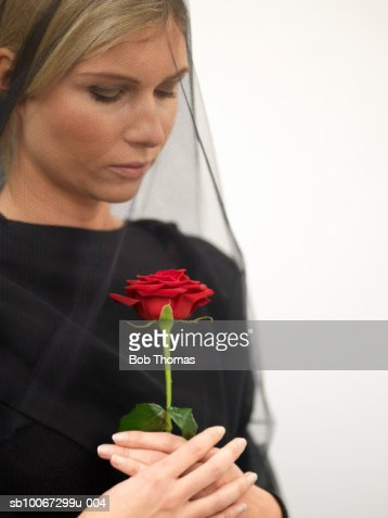Woman wearing veil holding rose, close-up : Foto stock