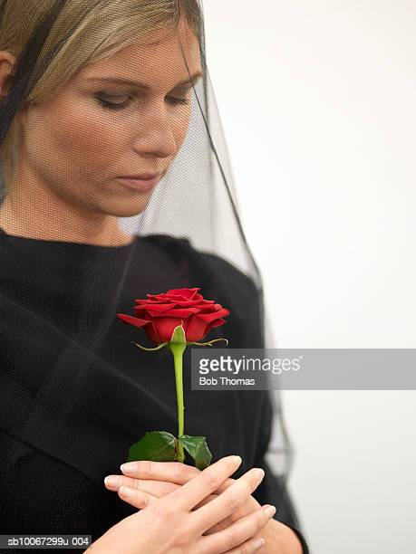 Woman wearing veil holding rose, close-up