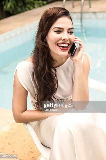 Woman wearing white dress on cell phone, laughing