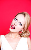 woman wearing white dress on red background licking her lips