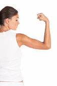 Beautiful woman flexing biceps - high key shot in studio