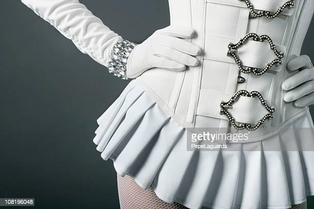 女性を着て、ホワイトレザーのコルセットとパッティング手を当てる