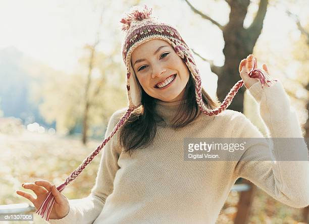 Woman Wearing Winter Clothing and Holding Woollen Hat