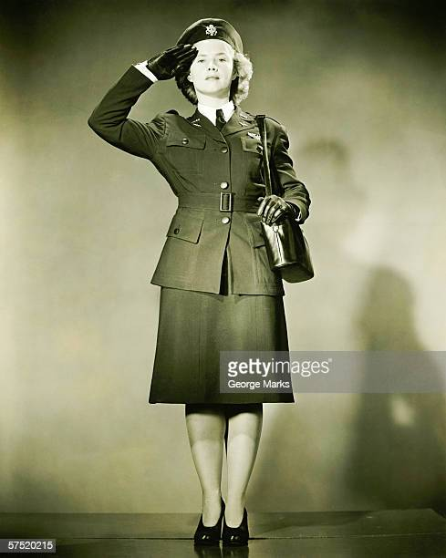 Woman wearing World War II uniform saluting in studio, (B&W), portrait