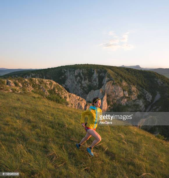 Woman wearing yellow jacket and red shorts running in nature