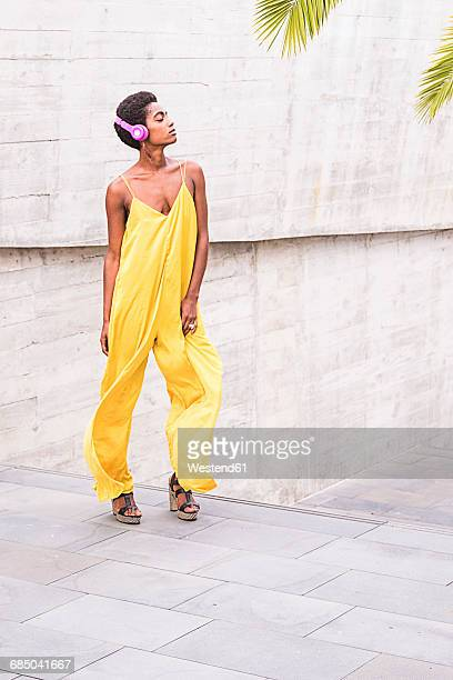 Woman wearing yellow jumpsuit listening music with headphones