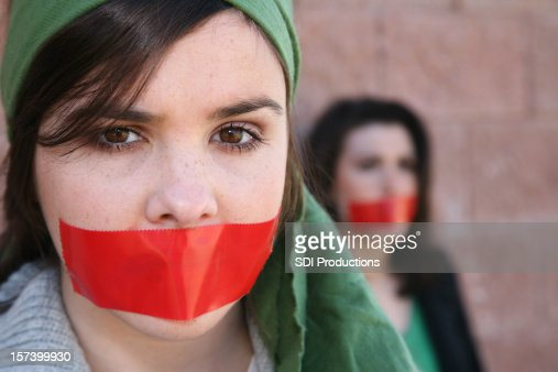 Woman Wearring A Head Scarf With Red Tape On Mouth