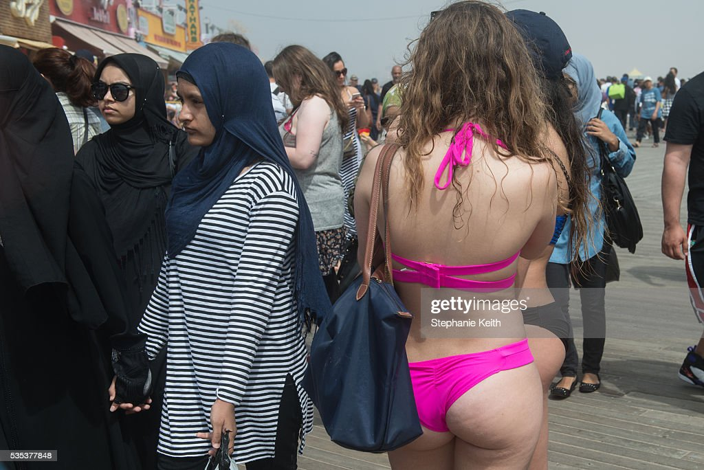 A woman wears a bikini near women wearing Muslim headscarves on the boardwalk in Coney Island on May 29, 2016 in the Brooklyn borough of New York City. New York City is experiencing higher than average temperatures for the holiday weekend.