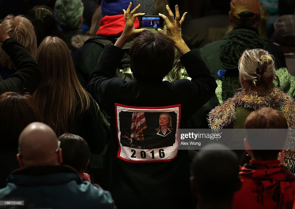 A woman wears a coat with a sign of 'Hillary Clinton for 2016' as she watches U.S. Vice President Joseph Biden participates during a Unite America in Service event on the National Day of Service as part of the 57th Presidential Inauguration January 19, 2013 at the DC Armory in Washington, DC. Vice President Biden and his family joined volunteers to pack care kits filled with necessities for deployed U.S. Service Members, Wounded Warriors, Veterans and First Responders.