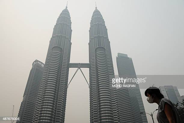 A woman wears a face mask as Malaysia's iconic Petronas Twin Towers are seen shrouded by haze in Kuala Lumpur on September 11 2015 The thick haze...