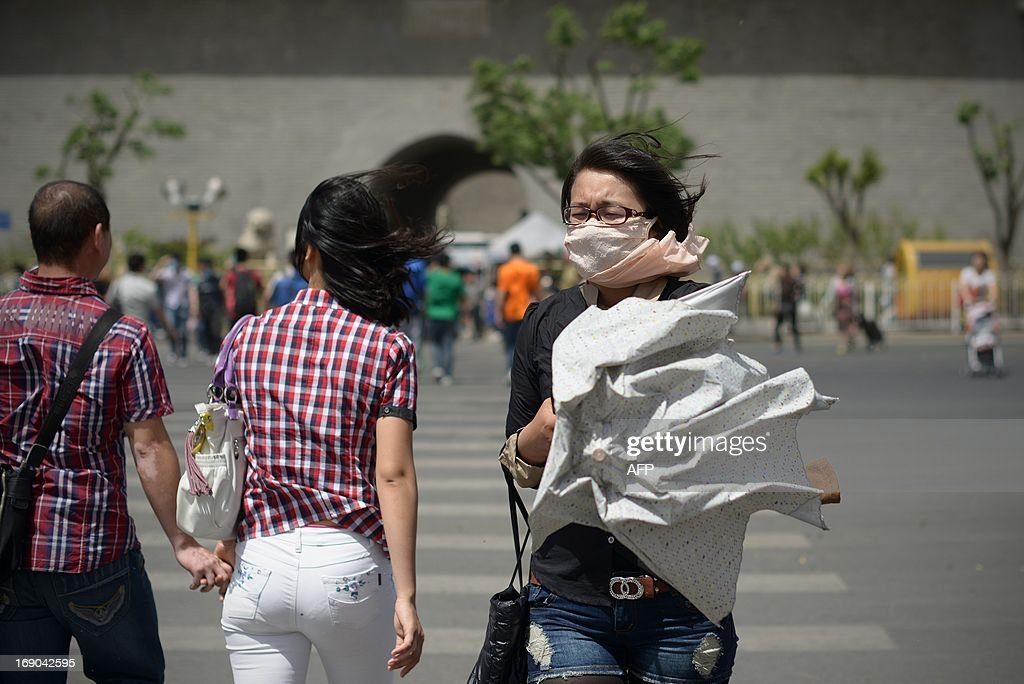 A woman (R) wears a face mask as she makes her way along a street in Beijing on May 19, 2013. China will more than double the number of cities covered by air quality monitoring, as part of efforts to tackle heavy smog that has sparked huge public anger. Swathes of acrid haze have repeatedly shrouded large parts of the country in recent months, provoking outrage among Internet users and unusual outspoken calls for action, in the state-run media.