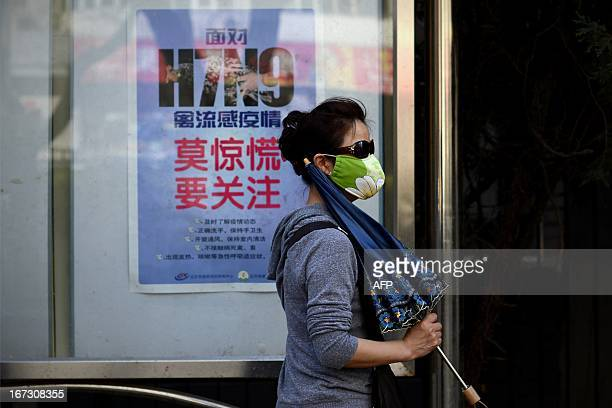 A woman wears a face mask as she walks past a poster showing how to avoid the H7N9 avian influenza virus by a road in Beijing on April 24 2013...