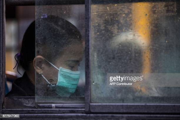 A woman wears a face mask whilst taking a bus in Yangon on July 26 2017 Two people including a pregnant woman have died from swine flu in Yangon this...