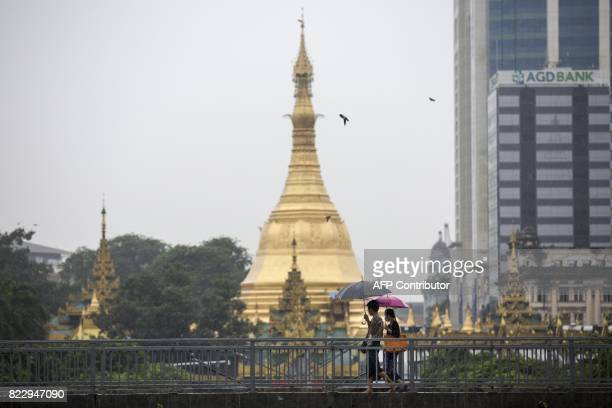 A woman wears a face mask whilst walking with a friend past Sule Pagoda in Yangon on July 26 2017 Two people including a pregnant woman have died...