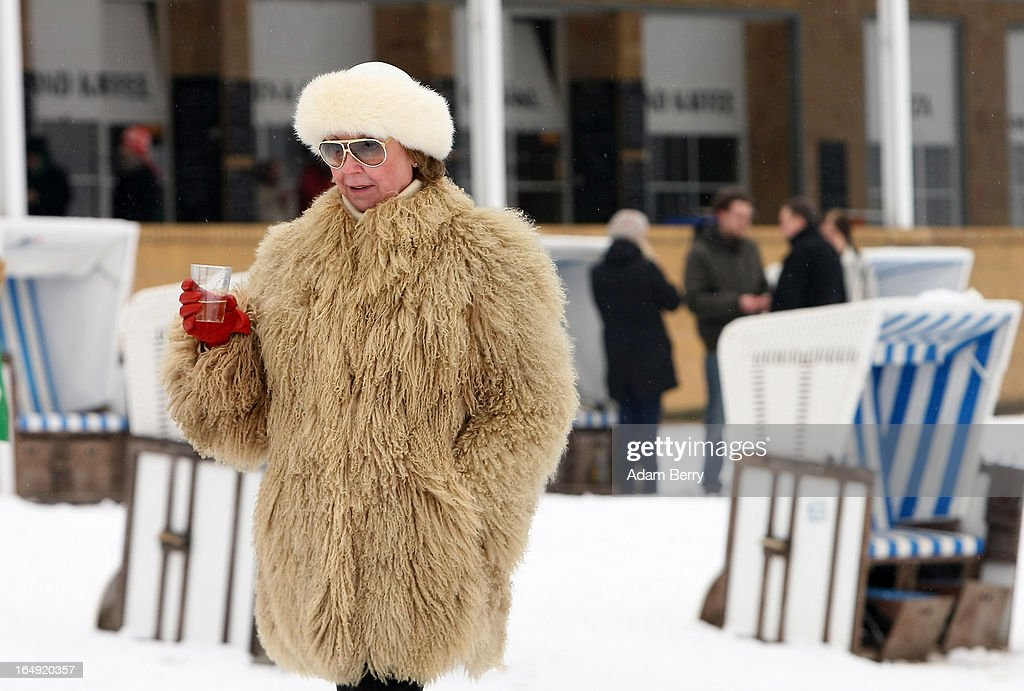 A woman wears a fur coat and hat while drinking sparkling wine as she walks on the snow-covered Strandbad Wannsee beach during its opening day for the year on March 29, 2013 in Berlin, Germany. Despite continued unseasonably cold temperatures in the country, organizers opened the beach for bathers in time for the last weekend of March, when Easter Sunday is expected to be colder than the previous Christmas Day had been.