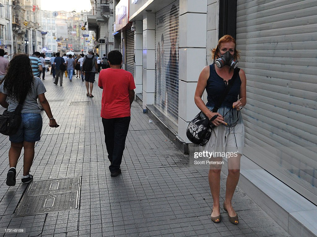 A woman wears a gas mask as Turkish police battle anti-government protestors along the Istiklal shopping street near Taksim Square on July 8, 2013 in Istanbul, Turkey. The protests began in late May over the Gezi Park redevelopment project and saving the park trees adjacent to Taksim Square but swiftly turned into a protest aimed at Prime Minister Recep Tayyip Erdogan and what protestors call his increasingly authoritarian rule. The protest spread to dozens of cities in Turkey, in secular anger against Mr. Erdogan and his Islam-rooted Justice and Development Party (AKP).