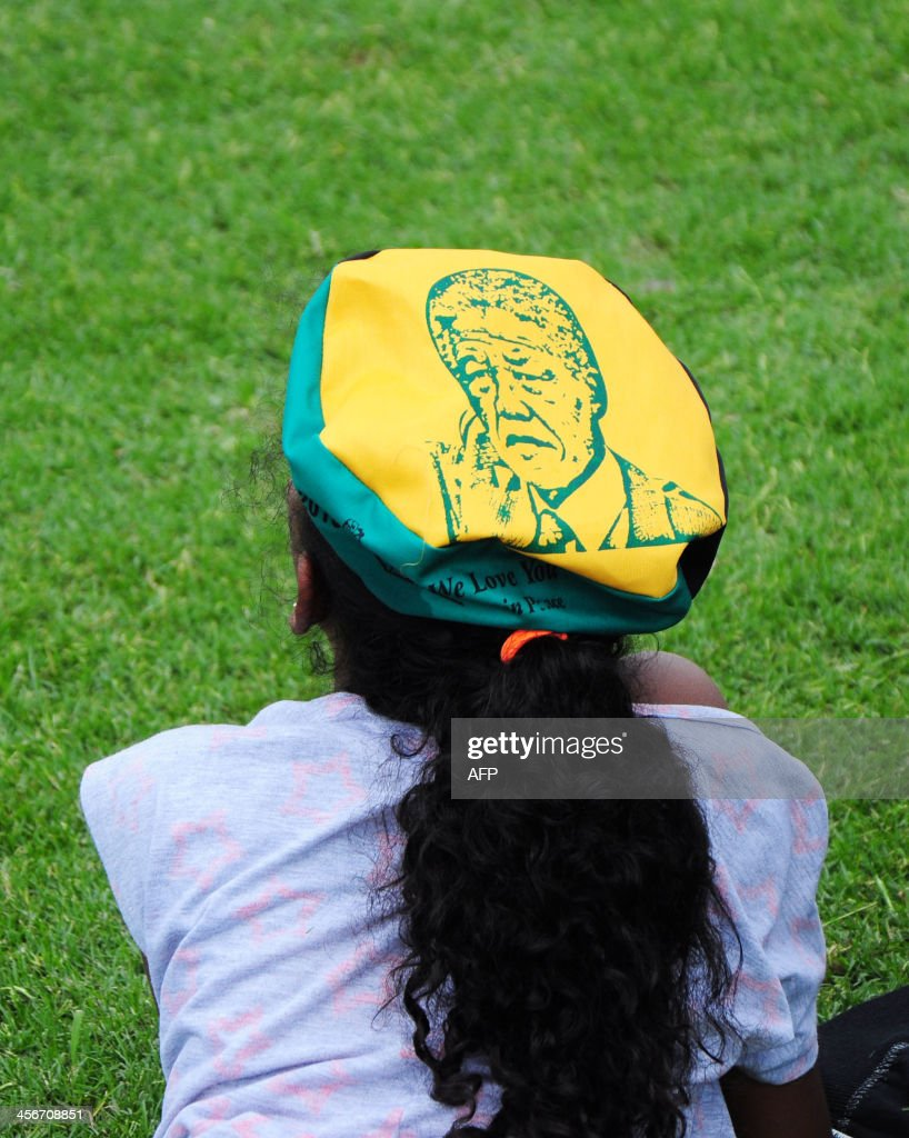 A woman wears a hat bearing a drawn portrait of late former South African President Nelson Mandela as people watch a live television broadcast of his funeral ceremony, on the day of Mandela's burial in his hometown, on December 15, 2013, in Durban. Mandela was buried near his homestead Qunu today, ending 10 days of national mourning and global tributes for the prisoner-turned-president who transformed his country and inspired the world. AFP PHOTO / Anesh Debiky