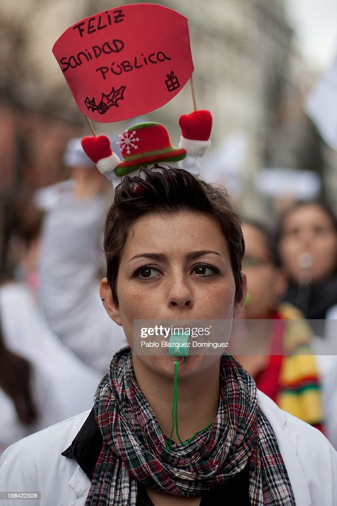 A woman wears a hat reading 'Merry public health care' amid other health workers during a demonstration against cuts on public health care and the privatization of medical centers and hospitals on December 16, 2012 in Madrid, Spain. In Madrid, doctors have already staged 11 days of strikes and all health workers unions are calling for a third 48 hour strike on December 19 and December 20. Around 4,000 operations have been suspended in Madrid since the medical strikes started.
