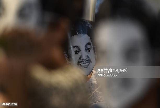 CORRECTION A woman wears a mask of Thai human rights activist Jatupat Pai Boonpattararaksa who was arrested in early December 2016 and charged with...