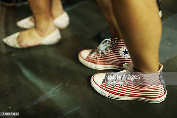 A woman wears a pair of American flag colored sneakers as she waits for the arrival of Republican presidential candidate Donald Trump to speak at the...