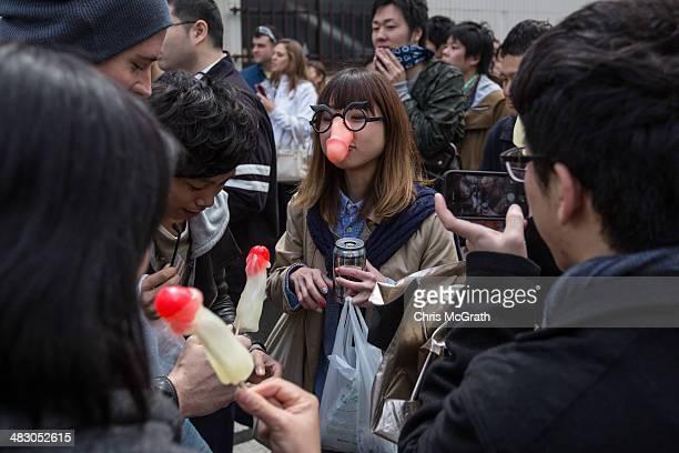 A woman wears a phallicshaped mask as friends eat phallicshaped lollipops at the Wakamiya Hachimangu shrine during Kanamara Matsuri on April 6 2014...