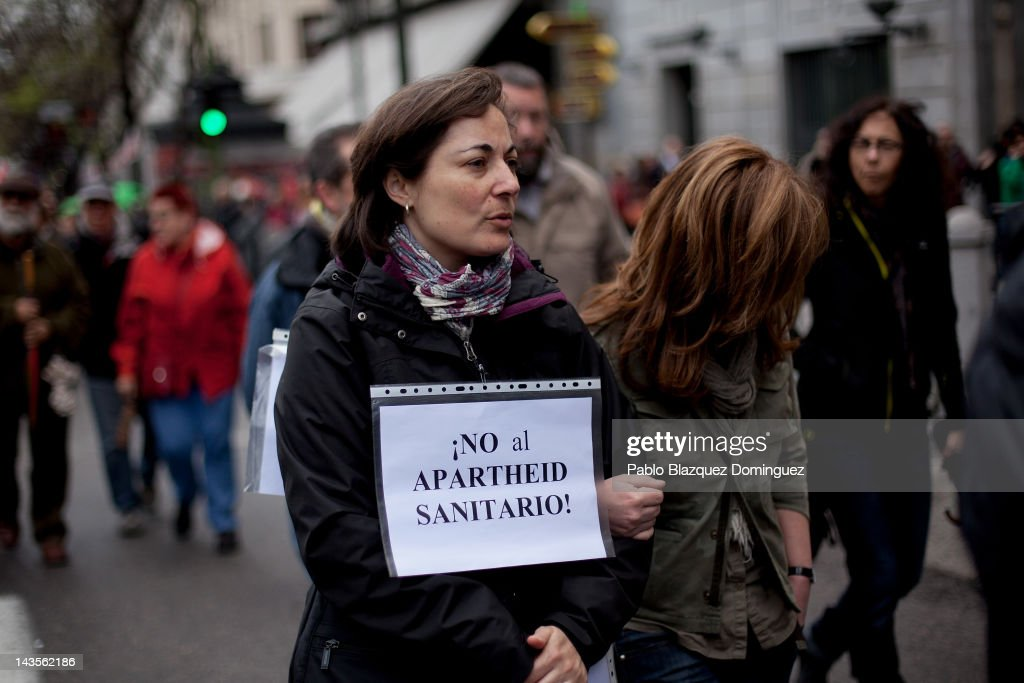A woman wears a placard that reads 'Not to the Apartheid in Health Services' during a demonstration organized by Unions against the financial cuts in health and education on April 29, 2012 in Madrid. Trade Unions CCOO and UGT called for a demonstration against the severe austerity plans of the Spanish government. This month unemployment has reached a record rate and the government has announced that immigrants with no legal status will not be covered by the health public services. The government aims to get the deficit down to 5.3 percent this year and 3.0 percent in 2013.