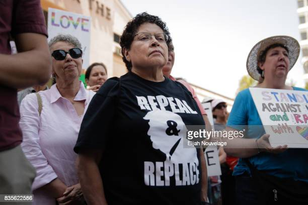 A woman wears a shirt advocating for the impeachment of President Donald Trump at a rally against white nationalism on August 19 2017 in Mountain...